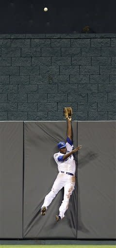Kansas City Royals center fielder Lorenzo Cain reaches for a solo home run hit by Texas Rangers' Adrian Beltre during the fourth inning of a baseball game, Thursday, Sept. 6, 2012, in Kansas City, Mo. (AP Photo/Charlie Riedel)