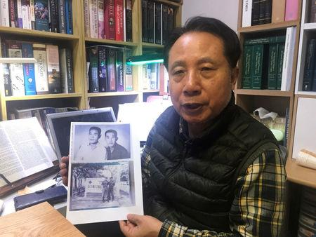 Ahn Yong-soo, whose brother was a South Korean prisoner of war captured by communist Vietnamese during the Vietnam War and sold to North Korean military officers, poses for photographs with a picture of his brother, at his home in Seoul, South Korea, February 12, 2019. Picture taken on February 12, 2019   REUTERS/Park Ju-min