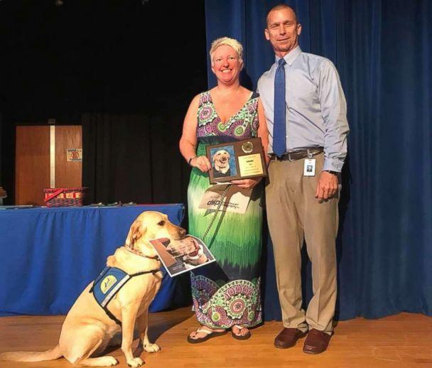 PHOTO: Principal Charlie Bynum of Orange City Elementary School seen in a recent photo as he and Heidi Watton present Linda the service dog with a recognition plaque. (Orange City Elementary School)