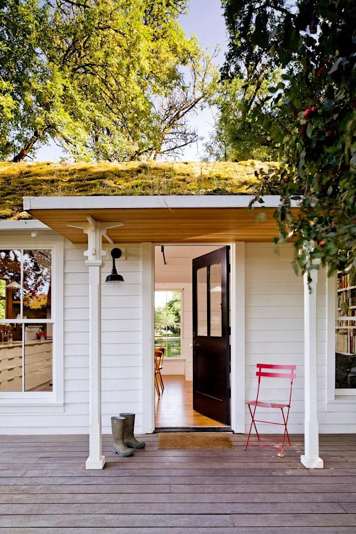 The front porch of the structure welcomes guests thanks in part to its fern-covered green roof.