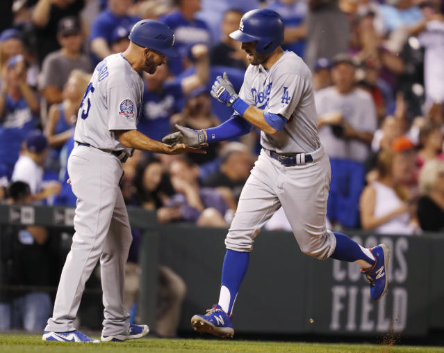 Los Angeles Dodgers third base coach Chris Woodward, left, congratulates Chris Taylor, who heads for home on a solo home run off Colorado Rockies relief pitcher Wade Davis during the ninth inning of a baseball game Thursday, Aug. 9, 2018, in Denver. (AP Photo/David Zalubowski)