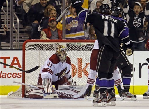 Los Angeles Kings center Anze Kopitar (11), of Yugoslavia, celebrates a goal by Dustin Penner, not shown, on Phoenix Coyotes goalie Mike Smith (41) in the first period of an NHL hockey game in Los Angeles Tuesday, March 19, 2013. (AP Photo/Reed Saxon)