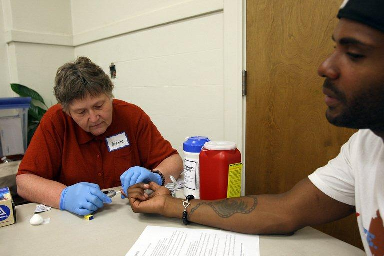 Nurse Dianne Wash takes a blood sample from Keri Anderson at a routine medical check in Los Angeles on July 10, 2012