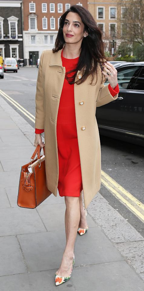 """<p>Clooney looked radiant while out in London on Wednesday in a red long-sleeve sheath dress that showed off just a hint of her baby bump (shop a similar style <a rel=""""nofollow"""" href=""""http://shop.nordstrom.com/s/eileen-fisher-silk-georgette-crepe-shift-dress-regular-petite/4568406?origin=category-personalizedsort&fashioncolor=SERRANO"""">here</a>). She paired the vibrant frock with floral pumps, a camel coat, and brown leather handbag for a speech at London's Chatham House, where she addressed war crimes in Iraq and Syria.</p>"""