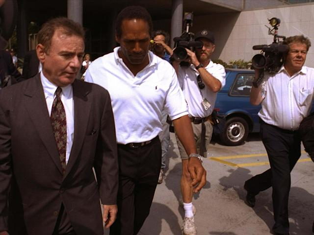 <p>Former NFL star O.J. Simpson, center, and his attorney Howard Weitzman, right, are besieged by the media as they leave police headquarters in downtown Los Angeles Monday, June 13, 1994, after Simpson was questioned in connection with the apparent murders of his ex-wife Nicole Brown Simpson and Ronald Lyle Goldman, 26, at the woman's Los Angeles condominium. (Photo: Michael Caulfield/AP) </p>