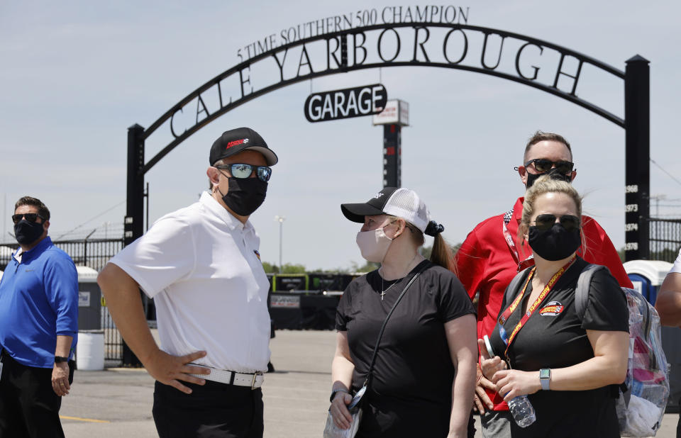Fans check out activity in the garage area before a NASCAR Cup Series auto race at Darlington Raceway, Sunday, May 9, 2021, in Darlington, S.C. It is the first time this year that fans are allowed back in the garage area. (AP Photo/Terry Renna)