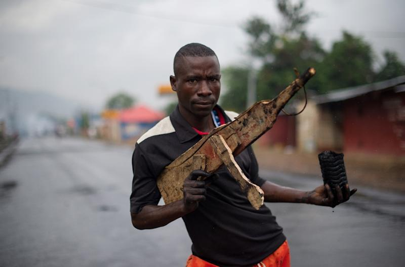 A man poses with a wooden rifle during protests in the Musaga neighbourhood in Bujumbura, Burundi, on May 5, 2015 (AFP Photo/Phil Moore)