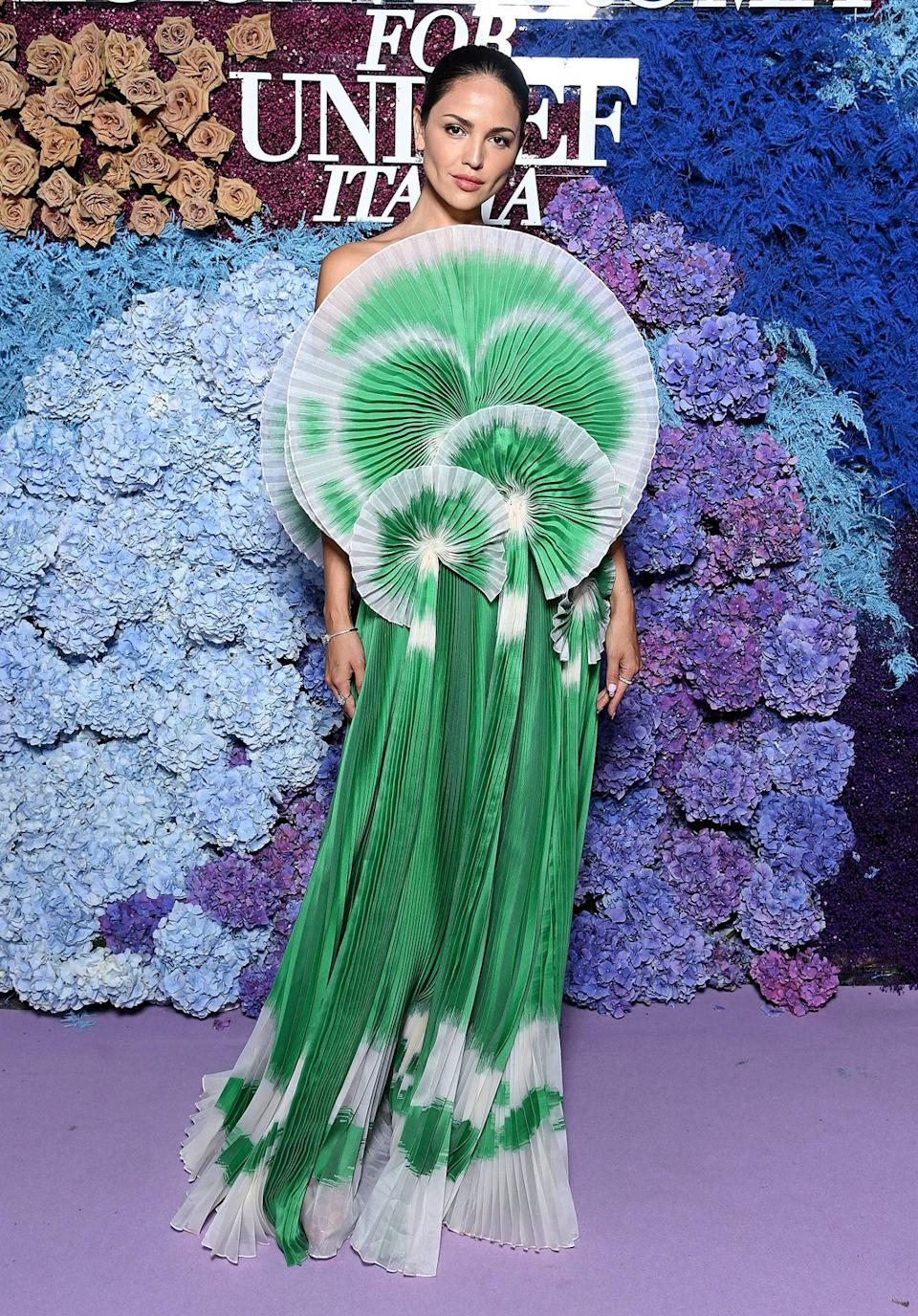 <p>arrives in a pleated green gown with circular fan bodice, plus Bulgari jewels. </p>