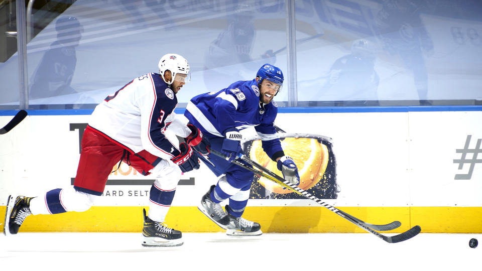 TORONTO, ONTARIO - AUGUST 11: Barclay Goodrow #19 of the Tampa Bay Lightning is chased by Seth Jones #3 of the Columbus Blue Jackets during the fourth overtime of Game One of the Eastern Conference First Round of the 2020 NHL Stanley Cup Playoff at Scotiabank Arena on August 11, 2020 in Toronto, Ontario. (Photo by Mark Blinch/NHLI via Getty Images)