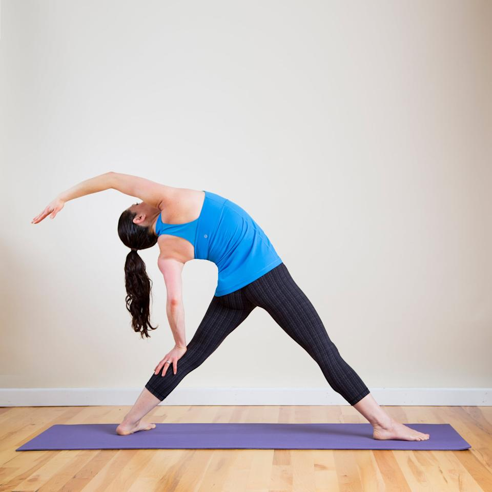<p>You'll feel this stretch all the way from your fingertips to your toes. It's a great stretch for the lats and the side of the torso.</p> <ul> <li>From a standing straddle position, turn the right toes out 90 degrees and the left toes in 45 degrees. </li> <li>Gently arch back and lower your left hand down, resting it on the back of your left leg. </li> <li>Raise your right arm overhead, feeling the stretch through the right side of the body. Continue to lower your hips, pressing your front knee forward so it's directly over your right ankle.</li> <li>Remain here for five complete breaths, then repeat on the other side.</li> </ul>