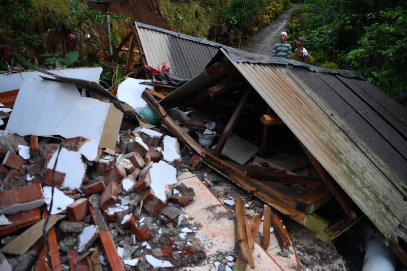 Men stand near a damaged house affected by an earthquake in Lumajang
