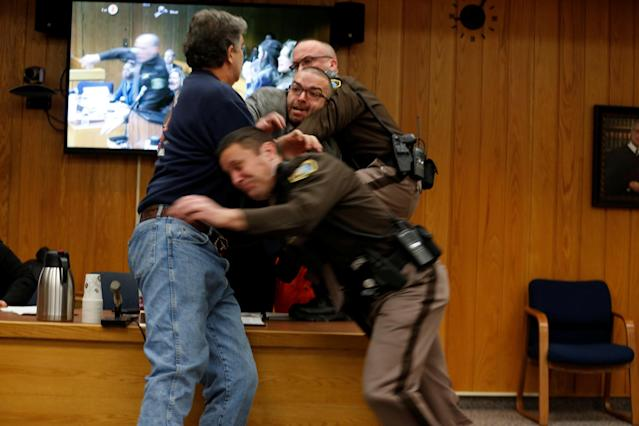 Randall Margraves (L) lunges at Larry Nassar,(wearing orange) a former team USA Gymnastics doctor who pleaded guilty in November 2017 to sexual assault charges, during victim statements of his sentencing in the Eaton County Circuit Court in Charlotte, Michigan, U.S., February 2, 2018. Picture 2 of 10 in series. REUTERS/Rebecca Cook