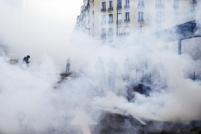 Tear gas envelopes protesters during a yellow vest demonstration marking the first anniversary in Paris, Saturday, Nov. 16, 2019. Paris police fired tear gas to push back yellow vest protesters trying to revive their movement on the first anniversary of the sometimes violent uprising against President Emmanuel Macron and government economic policies(AP Photo/Kamil Zihnioglu)
