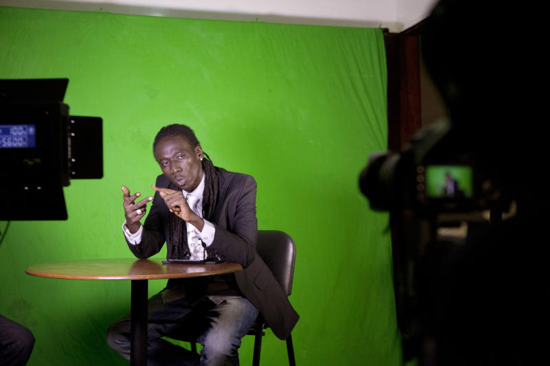 In this photo taken Tuesday, Sept. 10, 2013, guest commentator hiphop artist Duggy Tee raps about the week's news during a taping of the 'Journal Rappe,' in Dakar, Senegal. In the span of a program just five minutes long, Makhtar 'Xuman' Fall and his co-host Cheikh 'Keyti' Sene tackle, in rhyming verse, everything from the Middle East to local woes like the flooding that disproportionately hits poor suburbs of Senegal's capital. The news and commentary show, rapped in French and Wolof, went viral on YouTube earlier this year and now airs twice a week on Senegalese television. (AP Photo/Jane Hahn)