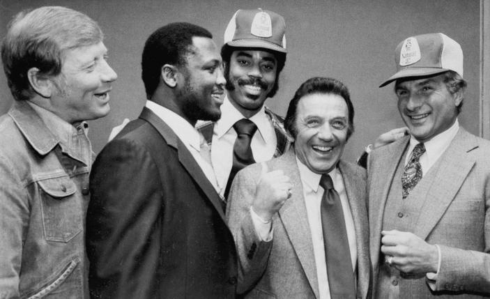FILE - In this March 1980 file photo, comedian Norm Crosby, second from right, gives a thumbs-up as he is surrounded by sports figures, from left, Mickey Mantle, Joe Frazier, Walt Frazier and Nick Buoniconti in New York, to launch a new ad campaign for a light beer. Crosby, the deadpan mangler of the English language who thrived in the 1960s, '70s and '80s as a television, nightclub and casino comedian, has died. He was 93. Crosby's daughter-in-law, Maggie Crosby, told the New York Times that the comic died Saturday, Nov. 7, 2020 of heart failure in Los Angeles. (AP Photo/Marty Lederhandler, File)