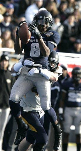 Utah State's Travis Reynolds (8) makes a reception against Toledo's Joey DeMartino (28) during the first half of an NCAA college football game on Saturday, Dec. 15, 2012, in Boise, Idaho. (AP Photo/Matt Cilley)