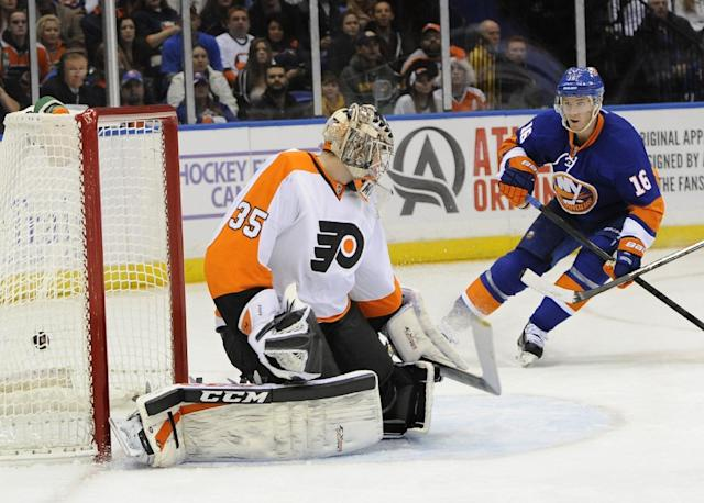 New York Islanders center Peter Regin (16) watches the puck shot by Frans Nielsen fly past Philadelphia Flyers goalie Steve Mason (35) to score in the second period of an NHL hockey game at the Nassau Coliseum on Saturday, Oct. 26, 2013, in Uniondale, N.Y. (AP Photo/Kathy Kmonicek)