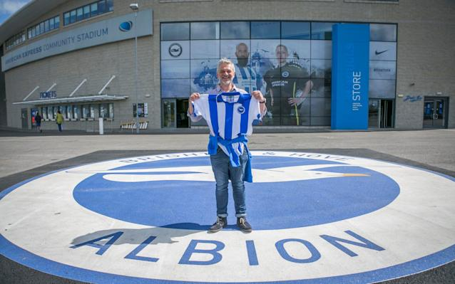 <span>Season ticket holder Martin Hill shows off the promotion season shirt he has just purchased at the Amex</span> <span>Credit: David McHugh for THE TELEGRAPH </span>
