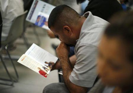 People read pamphlets as they wait in line at a health insurance enrollment event in Cudahy