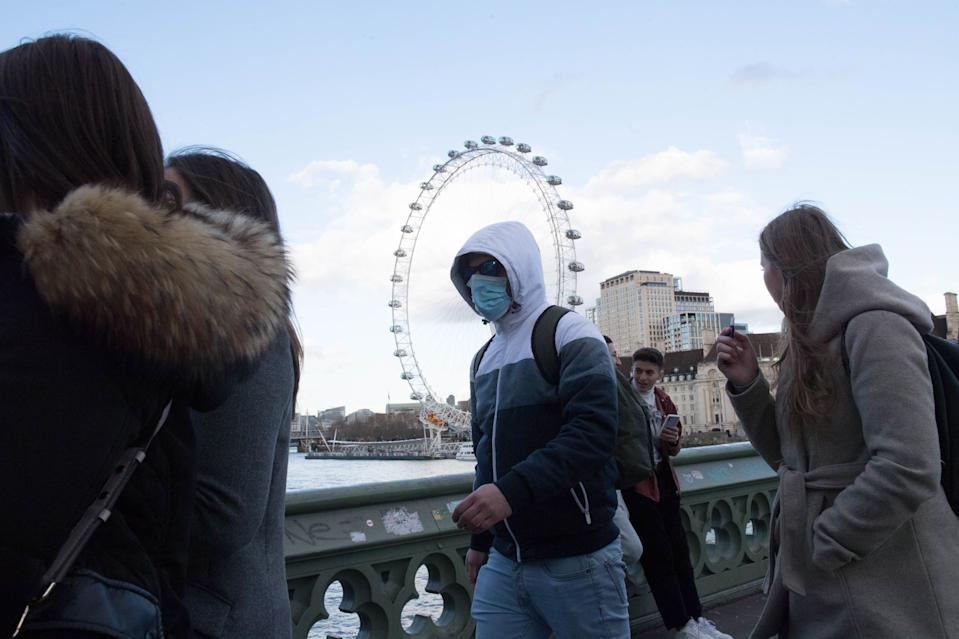A man wearing a face mask on Westminster Bridge in London, as Shadow Health Secretary Jonathon Ashworth says he would support shutting down cities to control the spread of coronavirus.