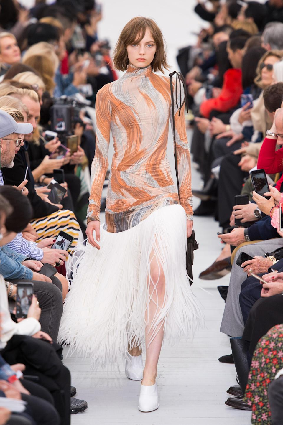 <p><i>Orange and white swirl dress with feather skirt from the SS18 Céline collection. (Photo: ImaxTree) </i></p>