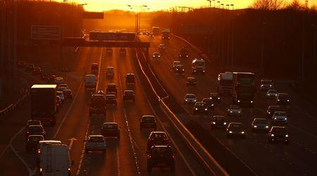 Traffic flows along the M56 motorway as the sun sets near Manchester, northern England