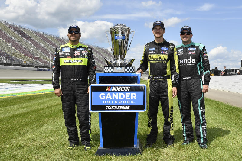 BROOKLYN, MICHIGAN - AUGUST 10: Matt Crafton, driver of the #88 Chi Chis/Menards Ford, Grant Enfinger, driver of the #98 ThorSport Racing/Curb Records Ford, and Johnny Sauter, driver of the #13 Tenda Heal Ford, pose with the playoff trophy after the NASCAR Gander Outdoor Truck Series Corrigan Oil 200 at Michigan International Speedway on August 10, 2019 in Brooklyn, Michigan. (Photo by Quinn Harris/Getty Images)