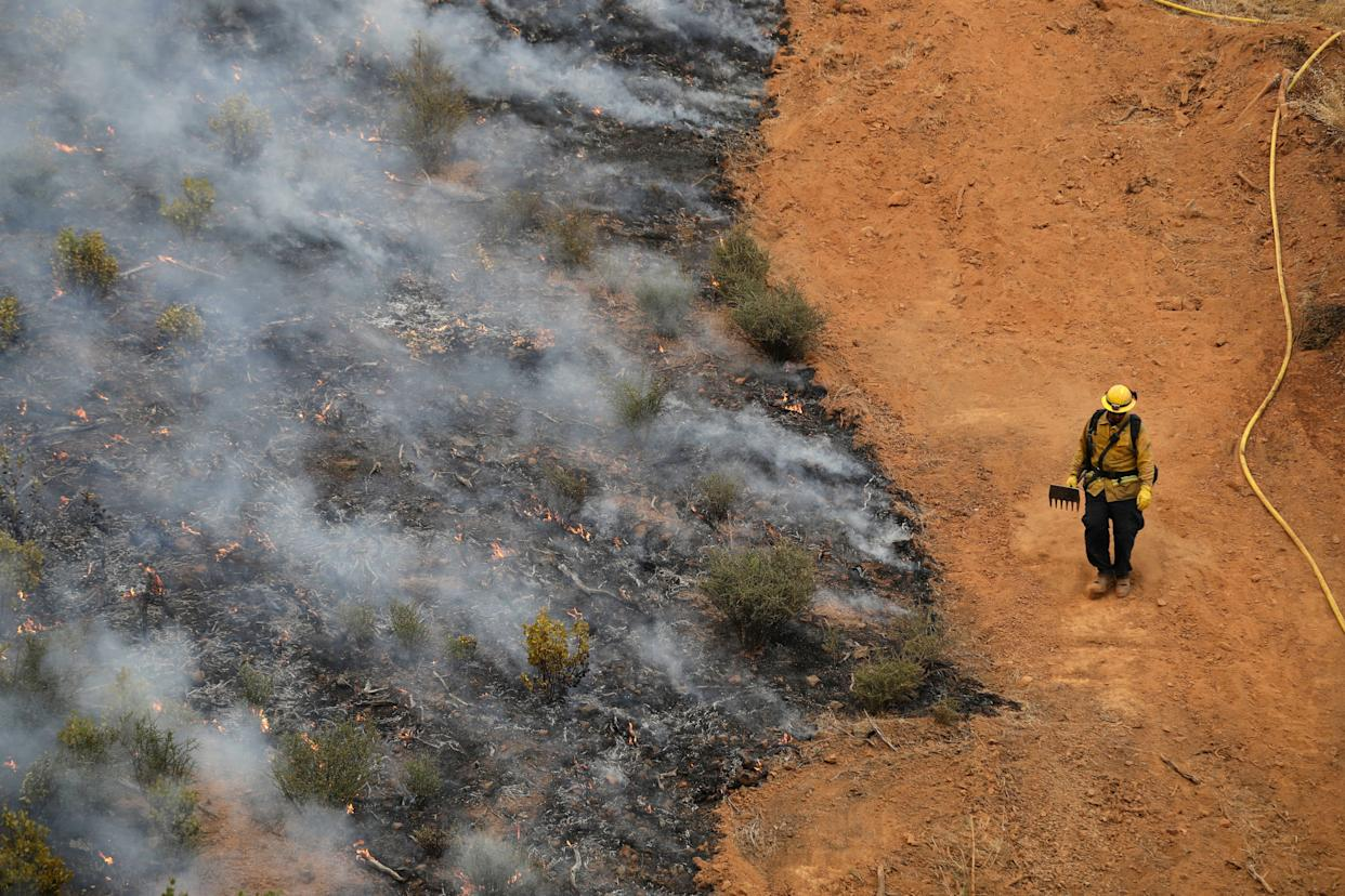 A firefighter walks along a containment line while battling a wildfire Saturday, July 28, 2018, in Redding, California.