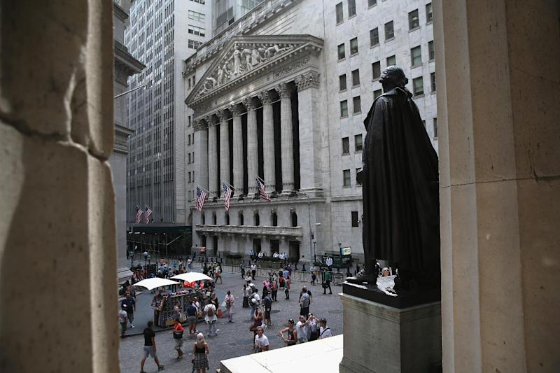 People walk in front of the New York Stock Exchange on July 30, 2014 (AFP Photo/John Moore)