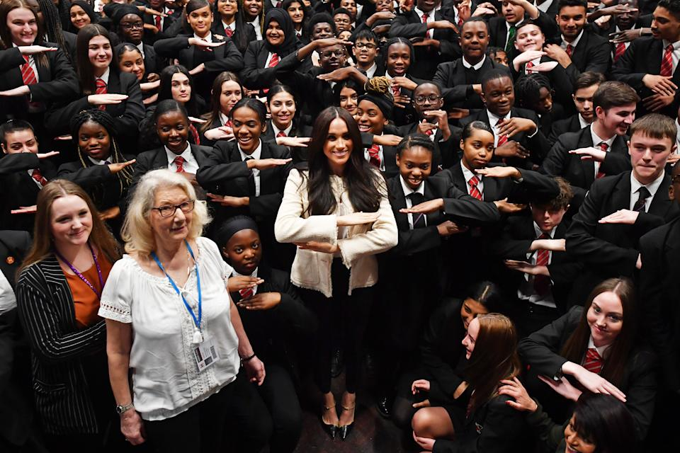 The Duchess of Sussex (centre) poses with school children making the 'equality' sign following a school assembly during a surprise visit to the Robert Clack Upper School in Dagenham, Essex, to celebrate International Women's Day. PA Photo. Picture date: Friday March 6, 2020. Meghan visited the school, addressing 700 pupils in an assembly ahead of the worldwide celebration of women's achievements on Sunday. Head boy Aker Okoye, 16, was later invited on stage with the duchess after swiftly volunteering to give his view on why men need to be involved in the fight for women's equality. See PA story ROYAL Meghan. Photo credit should read: Ben Stansall/PA Wire