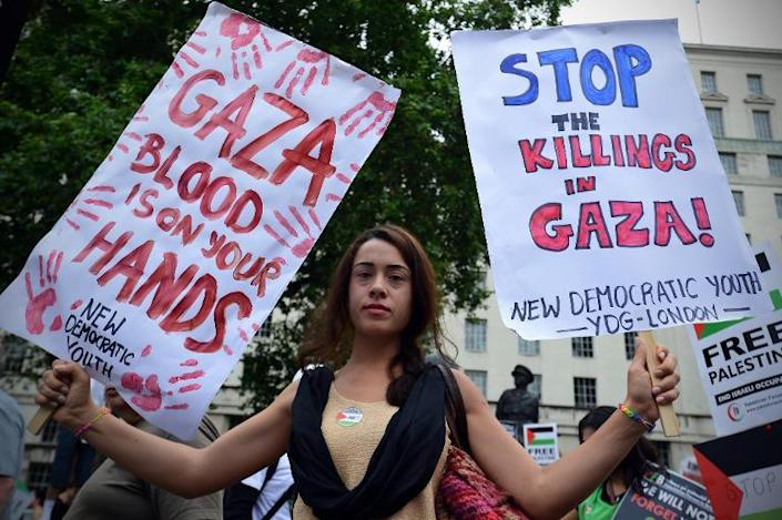 A woman holds placards as she takes part in demonstration against Israeli airstrikes in Gaza, during a demonstration in central London, on July 19, 2014 (AFP Photo/Carl Court)