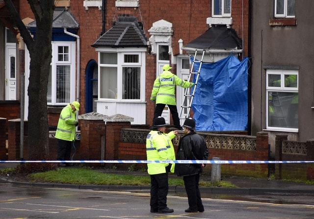 Police staff cover broken windows of a property on Pensnett Road, Brierley Hill, after the murder inquiry was launched