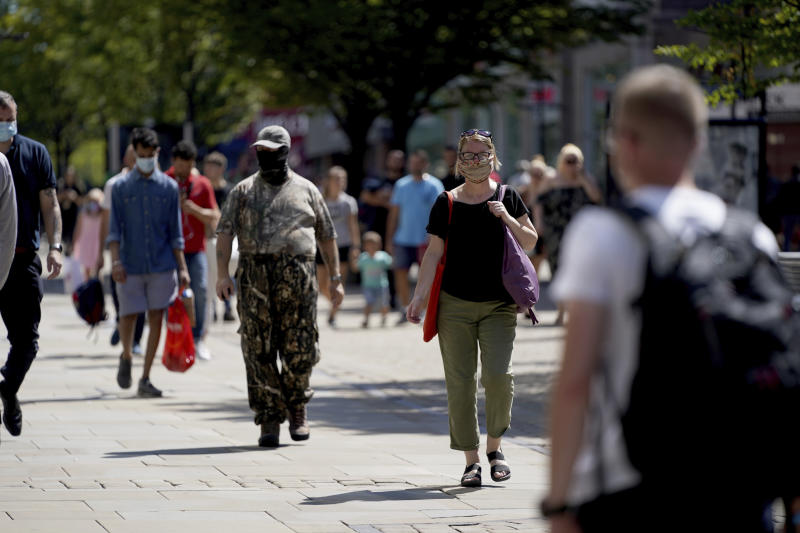 People walk wearing face masks to try to stop the spread of coronavirus in a shopping area in Manchester, northern England, Friday, July 31, 2020. The British government on Thursday night announced new rules on gatherings in some parts of Northern England, including Manchester, that people there should not mix with other households in private homes or gardens in response to an increase trend in the number of cases of coronavirus cases per 100,000 people. (AP Photo/Jon Super)