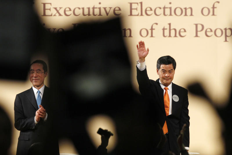 Former convener of Hong Kong's Executive Council Leung Chun-ying, right, declares his victory in the chief executive election of Hong Kong while former Hong Kong Chief Secretary Henry Tang stands next, with protesters in foreground hold placards Sunday, March 25, 2012. Leung was declared the semiautonomous territory's next chief executive by election officials after securing 689 votes from a 1,200-seat committee of business leaders and other elites. (AP Photo/Kin Cheung)