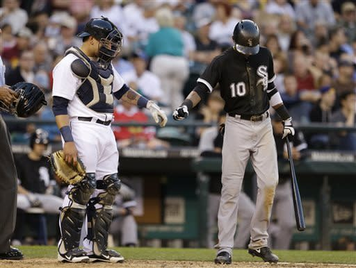 Seattle Mariners catcher Jesus Sucre, left, gets a fist-bump from Chicago White Sox's Alexei Ramirez after Sucre was checked by a trainer following being hit by Ramirez's bat on a swing in the fifth inning of a baseball game Tuesday, June 4, 2013, in Seattle. Sucre remained in the game through the inning, but left later on. (AP Photo/Elaine Thompson)