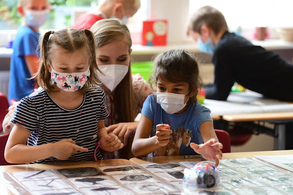 students wearing face masks sitting in a classroom with their teacher