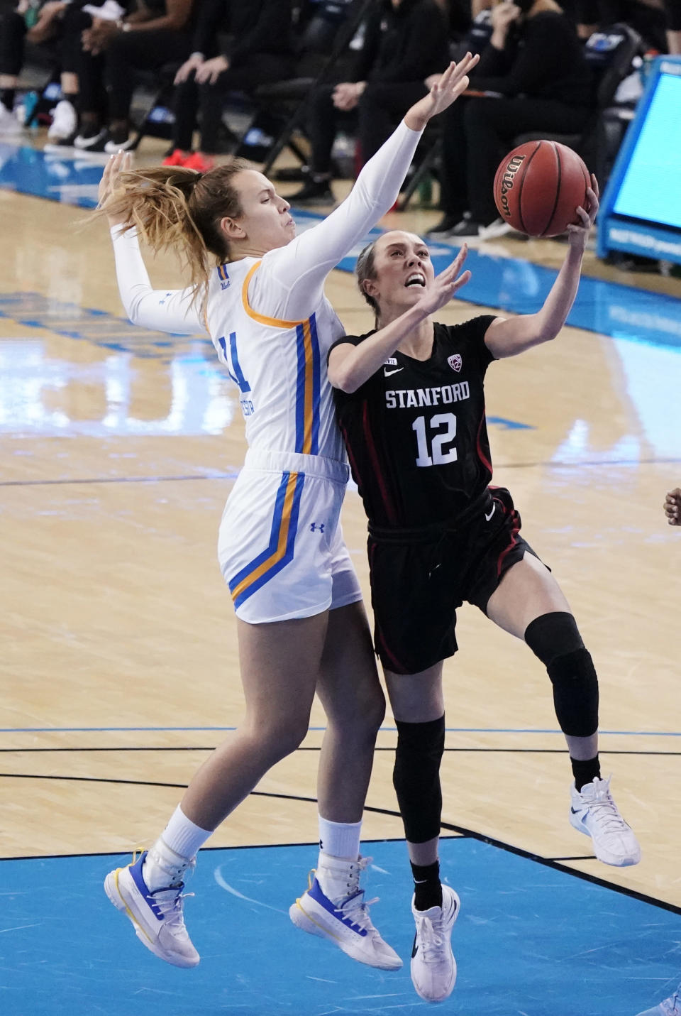 Stanford guard Lexie Hull (12) drives to the basket as UCLA forward Emily Bessoir defends during the first half of an NCAA college basketball game Monday, Dec. 21, 2020, in Los Angeles. (AP Photo/Marcio Jose Sanchez)