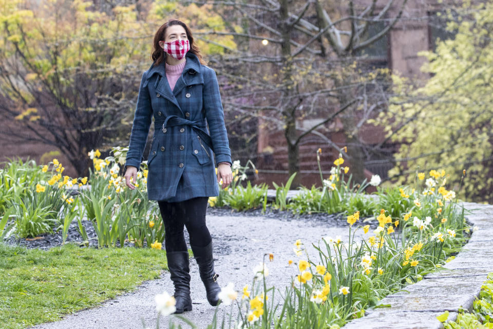 In this Friday, April 24, 2020, actress and part-time tour guide Megan Marod walks through the Hamilton Grange Historic site in the Hamilton Heights neighborhood of New York. Since those early days of the city's coronavirus outbreak, out-of-towners have become scarce. In just one late February day, Marod lost income from cancellations by student groups that typically flood the city in the early spring — her most lucrative months. (AP Photo/Mary Altaffer)