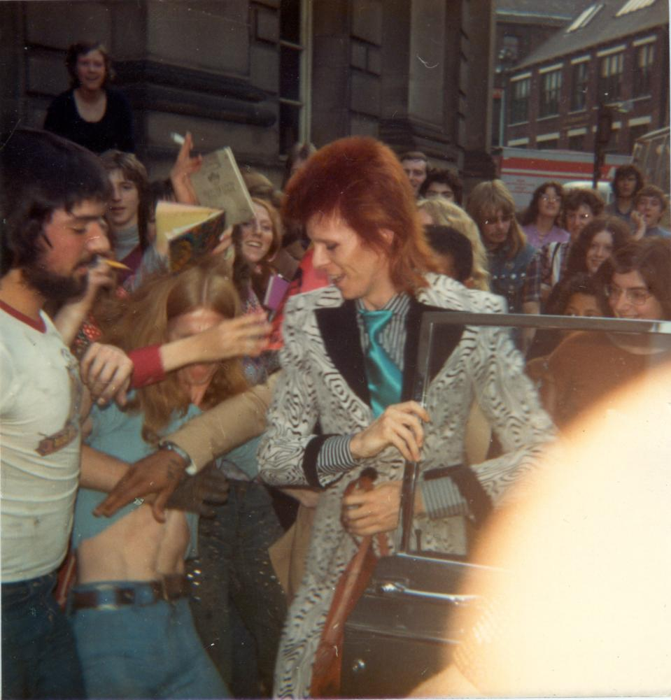 David Bowie gets out of a car surrounded by fans during his Ziggy Stardust era, Unite Kingdom, 1973. (Photo by Mark and Colleen Hayward/Getty Images)