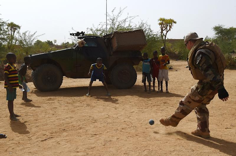 A French soldier from Operation Barkhane, an anti-terrorist operation in the Sahel, plays football with a group of young boys in Gao, northern Mali (AFP Photo/Philippe Desmazes)