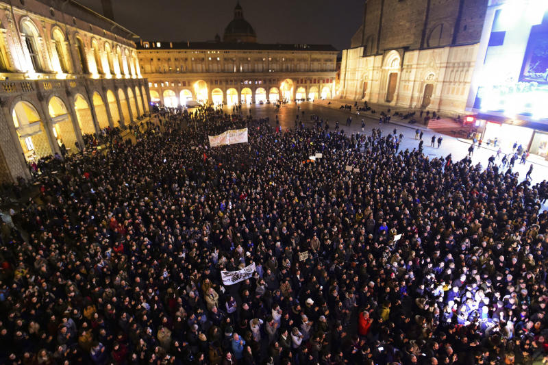 People gather to show support for Patrick George Zaki, in Bologna, Italy, Monday, Feb. 17, 2020.  Police detained Patrick George Zaki, 28, an Egyptian student at the University of Bologna in Italy, after he arrived in Cairo earlier this month on what was supposed to be a brief visit home. Zaki's arrest and detention have generated tremendous interest in Italy, the country where he's been studying. That's because of the 2016 death in Egypt of 28-year-old Italian researcher Giulio Regeni, whose battered body was found on a roadside on the outskirts of Cairo. (Massimo Paolone/Lapresse via AP)