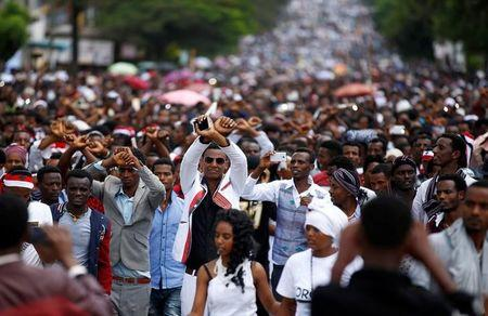 Demonstrators show the Oromo protest gesture sign during Irreecha, the thanks giving festival of the Oromo people in Bishoftu town of Oromia region, Ethiopia