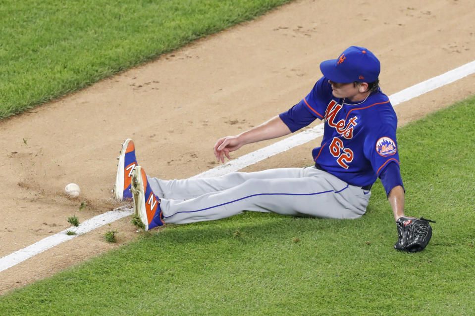 New York Mets relief pitcher Drew Smith (62) slips on the grass trying to reach an infield grounder hit by Thairo Estrada during the sixth inning of an exhibition baseball game against the New York Yankees, Sunday, July 19, 2020, at Yankee Stadium in New York. (AP Photo/Kathy Willens)