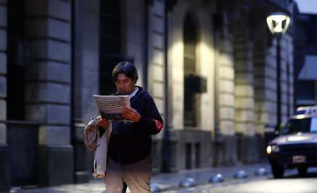 A man reads a newspaper as he walks in Buenos Aires' financial district early August 1, 2014. REUTERS/Marcos Brindicci