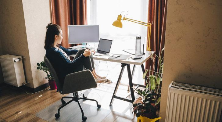 A photo of woman working on a computer at a desk in her home.