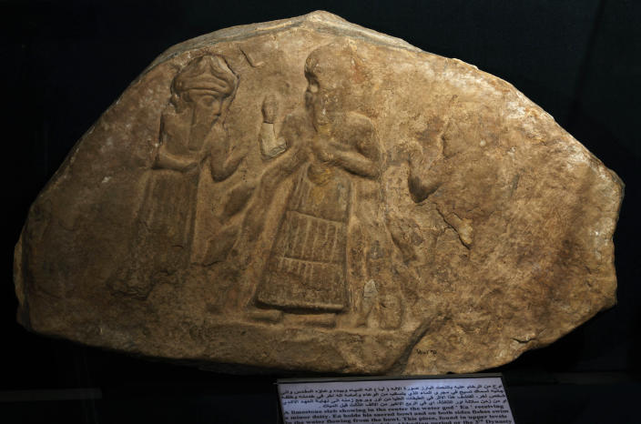 In this picture taken on Tuesday, April 2, 2013 a limestone slab showing in the center the water god, Ea, receiving a minor deity, is displayed at the national museum in Baghdad, Iraq. Ten years after Iraq's national museum was looted and smashed by frenzied thieves during the U.S.-led invasion in 2003 to topple Saddam Hussein, it's still far from ready for a public re-opening. Work to overcome decades of neglect and the destruction of war has been hindered by power struggles, poorly-skilled staff and the persistent violence plaguing the country, said Bahaa Mayah, Iraq's most senior antiquities official.(AP Photo/Hadi Mizban)