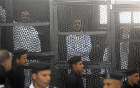 Political activists Ahmed Maher, Ahmed Douma and Mohamed Adel, founder of 6 April movement, look on from behind bars in Abdeen court in Cairo