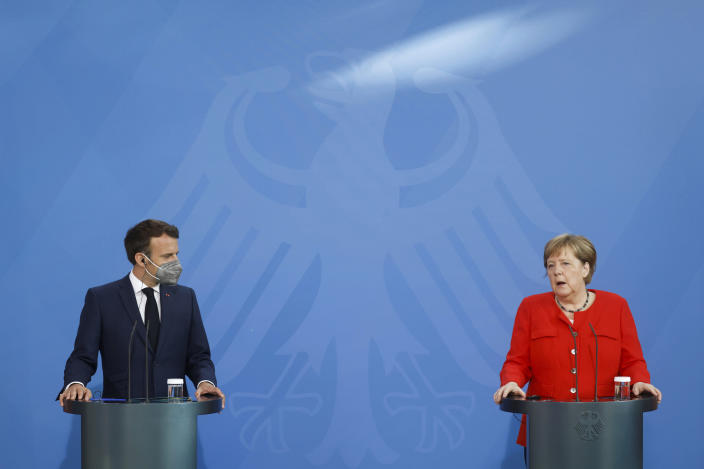 German Chancellor Angela Merkel, right, and French President Emmanuel Macron give a joint statement to journalists, at the chancellery in Berlin, Germany, Friday June 18, 2021. (Axel Schmidt/Pool via AP)