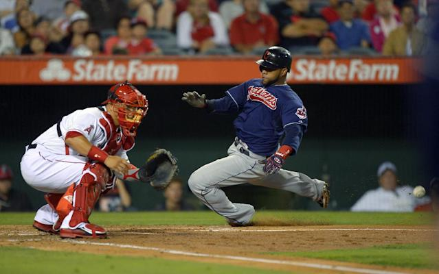 Cleveland Indians' Carlos Santana, right, scores on a sacrifice fly by Jason Giambi as Los Angeles Angels catcher Hank Conger takes a late throw during the fourth inning of their baseball game, Monday, Aug. 19, 2013, in Anaheim, Calif. (AP Photo/Mark J. Terrill)