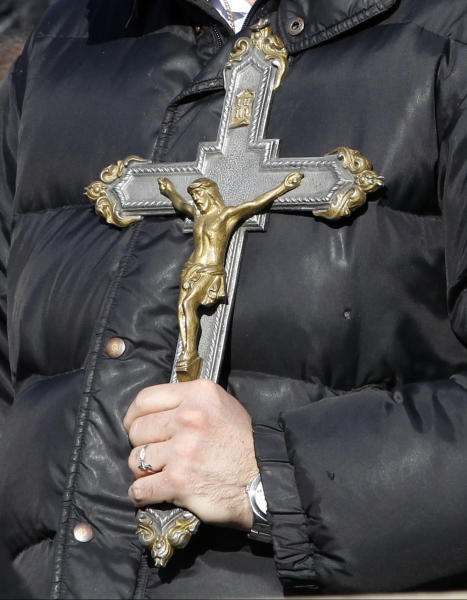A man holds a cross as he stands in St. Peter's Square at the Vatican, Wednesday, Feb. 27, 2013. Pope Benedict XVI is preparing for his final general audience, the weekly appointment he kept with the faithful and tourists to teach them about the Catholic faith. (AP Photo/Michael Sohn)